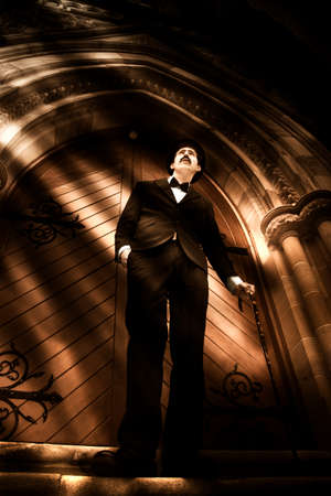 mortician: A Man Of Faith Stands At A Church Door While Rays Of Light Beam Down From Heaven Illuminating A Heavenly Scene Stock Photo