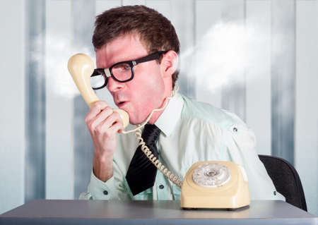 unskilled: Steaming angry nerd businessman holding retro phone cord around big red head while shouting out demands to incompetent and unskilled workers in a staff management conceptual Stock Photo