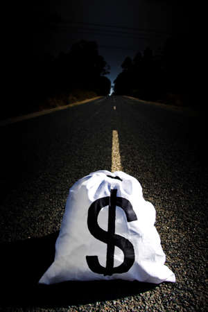 accrual: Banking And Investment Money Bag With Large Dollar Sign Sitting In The Middle Of A Highway On The Road To Wealth And Financial Gain Stock Photo