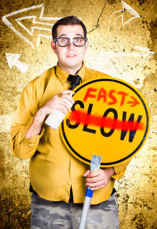 terminated: Male office worker holding slow sign painted over fast when showing direction to fast track productivity Stock Photo