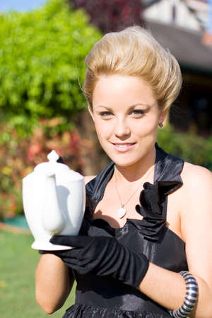 cupper: High Tea Woman Standing Outside In Her Front Garden Holding A Teapot During A High Tea Party