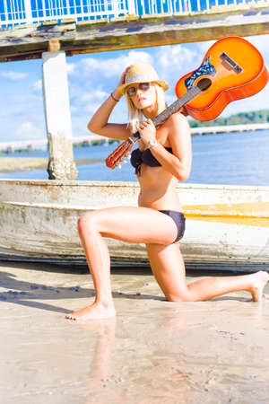 skiff: Rock And Roll Woman With Attitude And Music Instrument Posing Outdoors Next To A Beached Skiff In An Sunny Outdoor Holiday Lifestyle Portrait Stock Photo