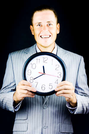 fulfilment: Smiling man in suit, holding a clock on black background