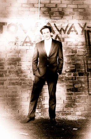 jaunty: Sepia Toned Faded Blotchy Vintage Photograph Of A Old Fashioned Gentleman In Suit Standing In Front Of A Brick Wall