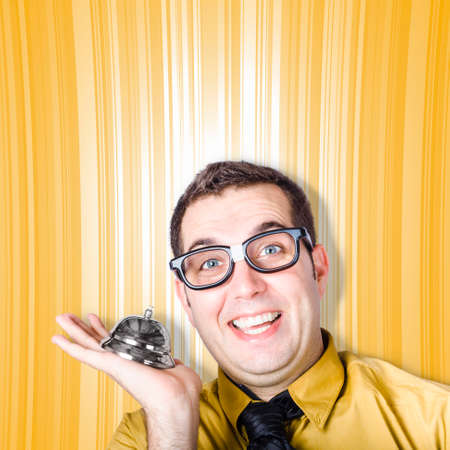 enquiry: Funny IT helpdesk employee holding desk service bell, ready to assist you with your enquiry Stock Photo