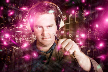 unplugged: Disconnected male DJ holding unplugged audio jack with confused expression in colourful nightclub Stock Photo