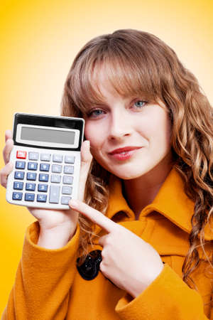 rueful: Attractive young woman with a rueful smile pointing to a calculator keypad with a blank display as she presents the sum total of her costs and expenditures on an orange studio background