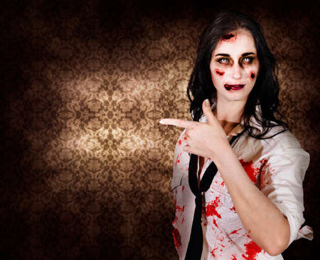 ghoulish: Terrifying marketing woman promoting dead space when pointing to grunge wallpaper inside a haunted house in a depiction of halloween advertising Stock Photo