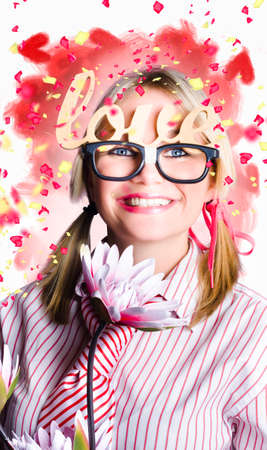 girl holding flower: Funny portrait of a romantic nerd girl holding flower while balancing words of love in falling confetti Stock Photo