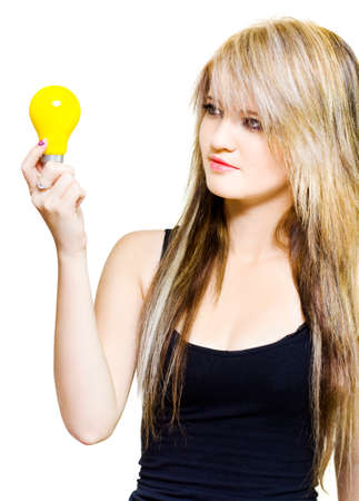 ingenuity: Studio photograph of a attractive young woman holding a light bulb while in thought in a concept of ingenuity, genius and innovation on white background