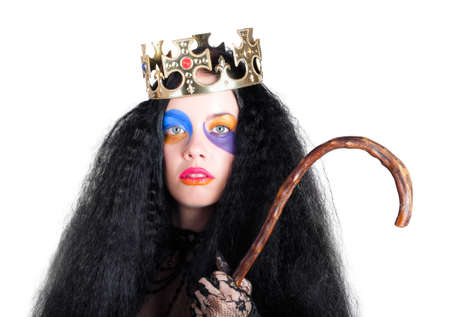 sombre: Queen with colorful face make-up, long black hair and golden crown holding a walking stick Stock Photo