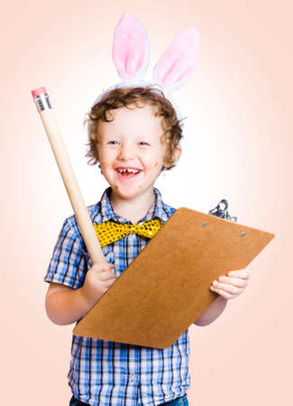 writing activity: Laughing young easter child holding clipboard and pencil when writing a activity list on easter holiday recreation Stock Photo