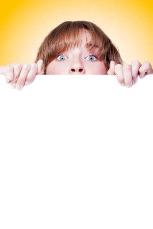 Mujer mira a escondidas sobre un cartel blanco en blanco con sólo sus ojos visibles como ella llama su atención sobre el copyspace blanco debajo Foto de archivo
