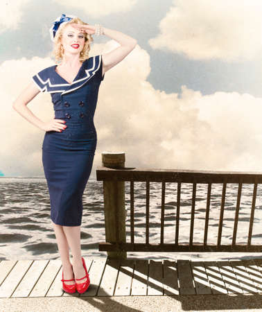 Fine art photo of a beautiful young pin-up woman with vintage make-up and blond hairstyle saluting on vacation departure dock