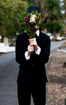 clandestine: Grieving Man Burying Face In Funeral Flowers At Cemetery Remembrance Service Stock Photo