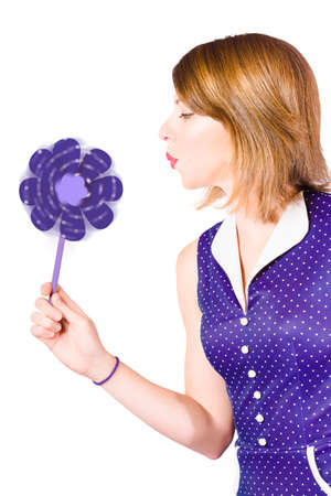 perinola: Side on profile photograph of a pretty pin up girl with short hairstyle blowing on purple pinwheel or whirligig. Fun with the elements on white Foto de archivo