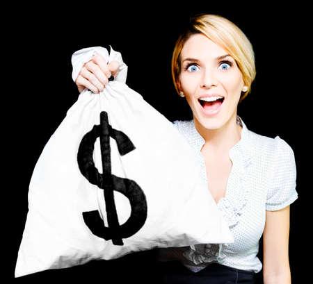 signo pesos: Mujer de negocios Euphoric ojos muy abiertos por la sorpresa y la emoción hasta la celebración de una ganancia inesperada de una bolsa de dinero de peluche llena de dólares como se imagina su nueva riqueza y la opulencia Foto de archivo