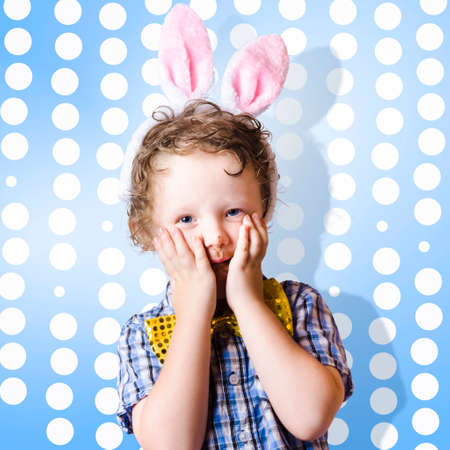 astounded: Adorable little kid with a surprised look wearing bunny rabbit ears on blue easter egg background Stock Photo