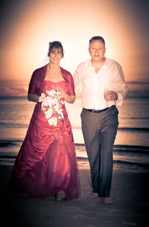 in loving memory: Smiling Bride And Groom Walk Up The Beach In Front Of A Sunset After A Beautiful Beach Marriage