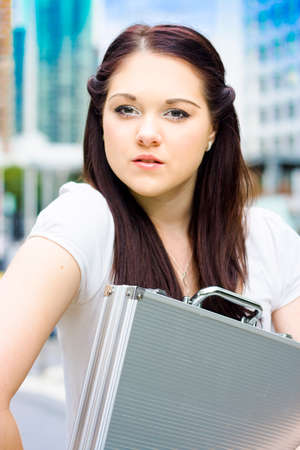 city location: Attractive Female Architect Consultant With Brunette Hair Carrying Plans In Briefcase At City Location During An Onsite Building Inspection For Quality Assurance Stock Photo