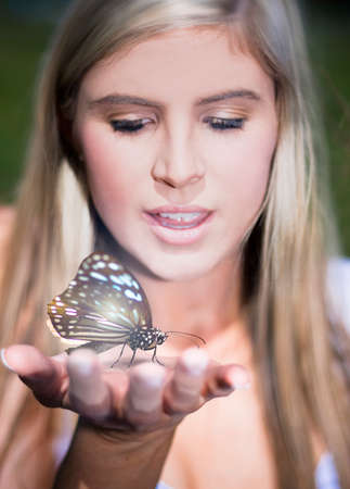 outstretched hand: Portrait Of A Pretty Young Woman Holding A Large Butterfly In Her Outstretched Hand Stock Photo