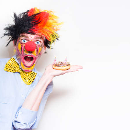 birthday clown: Shocked Happy Birthday Clown Holding Doughnut Party Cake With Two Candles During A Childs Birthday Party On Copy Space Background