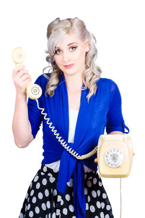 handing over: Attractive blond female secretary handing over the receiver on vintage yellow phone, its for you Stock Photo