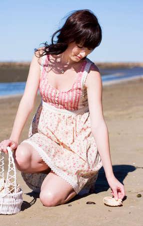 en cuclillas: Activo Mujer Hermosa En Un Recreación vacaciones sostiene una cesta de caña durante la percepción de Shells By The Shoreline Beach