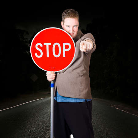layoffs: Disruptive business man signalling a traffic hold up when holding a stop road sign on highway. Under construction