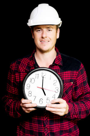 work workman: Smiling building workman holding a round clock showing five pm home time as he prepares to knock off from his shift at work