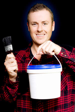 redecorating: Young DIY home owner holding up a tub of paint and a brush as he smiles in anticipation of redecorating and renovating his house