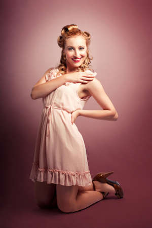 kneeling woman: Full Body Pinup Portrait Of A Kneeling Young Beautiful Caucasian Girl Posing In Pink Retro Style Dress Stock Photo
