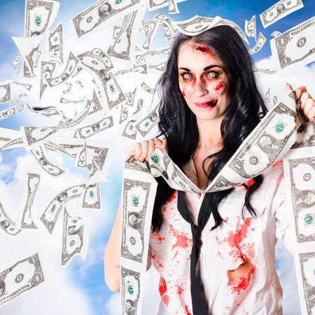scrooge: Female zombie person celebrating massive accumulated wealth in the heavens above with unspent life earnings in a depiction of the saying TO BE THE RICHES PERSON IN THE GRAVEYARD Stock Photo