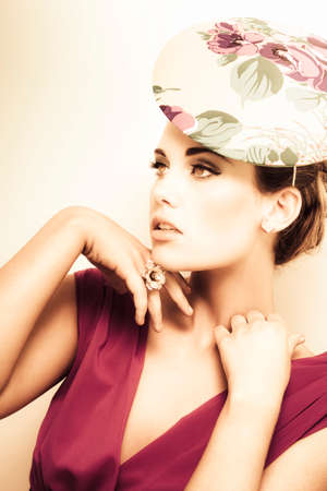 high class: woman wearing v-neck blouse and floral hat, flower ring on her finger, hands touching her neck