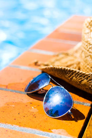 water pool: Summer Pool Party. A pair of sunglasses and summer straw hat resting on bricks alongside a sparkling pool Stock Photo