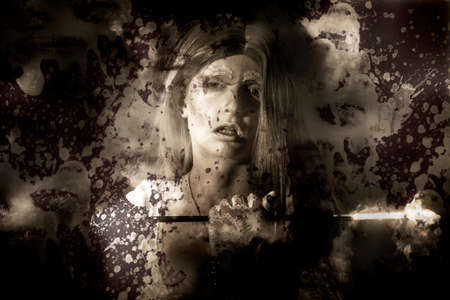 reflection mirror: Dark fantasy portrait of an evil vampire woman with cigarette holder looking into a blood smeared mirror reflection Stock Photo