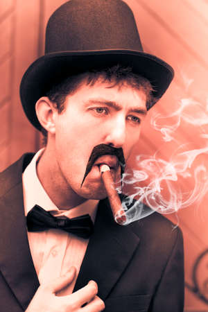 cigar smoke: Victorious Man Smokes A Cigar In A Celebration Of Vintage Joy After A Retro Formal Victory Stock Photo
