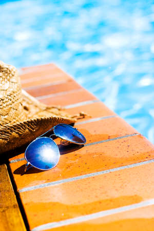 bather: Pair of sunglasses with lens sun flare and straw hat abandoned by a bather on wet tiles alongside a sparkling swimming pool in a summer vacation concept