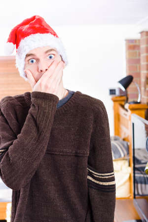 forgot: Gasping man standing indoor in a home interior wearing Christmas hat, covering mouth in shock. Xmas surprise