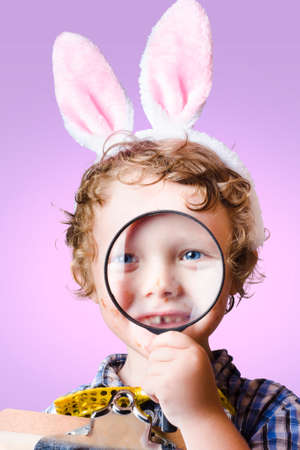 pink rabbit: Face of a cute kid wearing pink rabbit ears searching through looking glass during a search and find, easter hunt of discovery