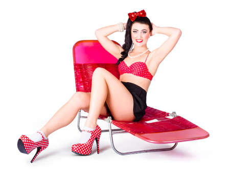 brassiere: Glamour pin-up girl relaxing on pink holiday recliner chair in high class heels and polkadot brassiere. Retro summer fashion Stock Photo