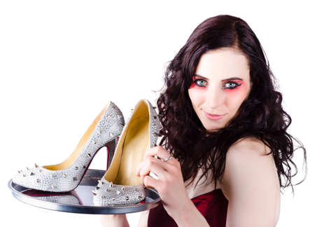 selling service: Beautiful woman selling exquisite high heel shoes with spikes on silver service platter