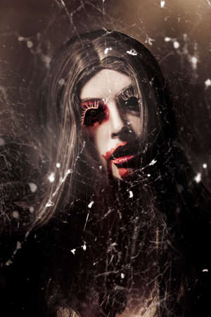 disturbing: Female face of dark horror lurking in the shadows of darkness beneath the spin of spider webs. Eye of the black widow