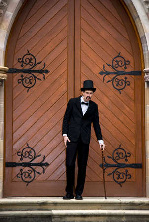 ie: An Old And Frail Mortician Steadies Himself With A Cane As He Stands At The Front Of A Closed Church Door