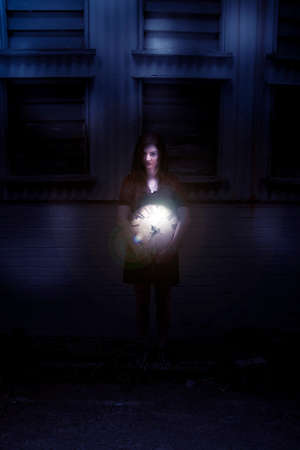 dimly: Woman Holding A Clock At Night In From Of A Dark Building Background