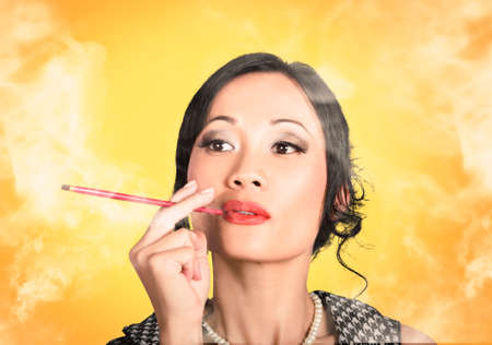 asian lady: Beautiful reto Asian lady smoking with cigarette holder on yellow background Stock Photo