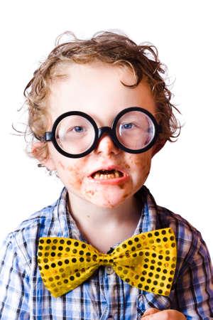 dientes sucios: Retrato de muchacho divertido con grandes gafas de pasta negra y con su cara cubierta en chocolate Foto de archivo