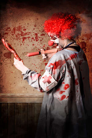 clinical trial: Scary medical clown injecting horror into an amputated limb when practising a vaccination clinical trial Stock Photo