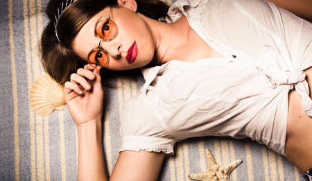 eyewear fashion: Classic retro vacation portrait of a pin-up woman wearing teashade designer optical frames from 1970 while lying on a beautiful tropical beach. Eyewear fashion model