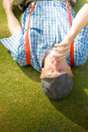 decides: The Course Of Golf Romance Begins When A Man Lying On His Back On A Golfing Green Decides To Kiss His Golf Ball After A Sinking His First Hole In One Stock Photo